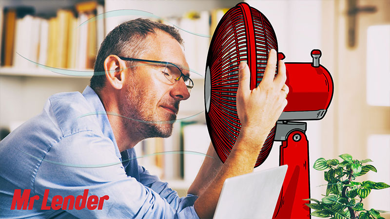 Man using a fan to cool down